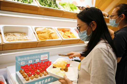 Customers choose the ingredients for their meal at a Hope Tree restaurant which is offering plant-based meatballs produced by Zhenmeat in Beijing