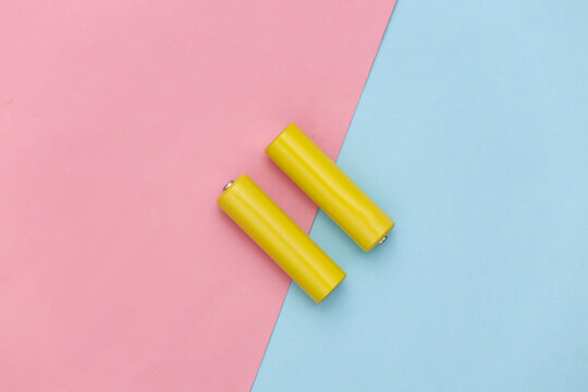 Two yellow AA batteries on pink blue pastel background. Top view