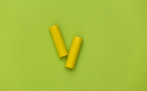 Two yellow AA battery on green pastel background. Top view