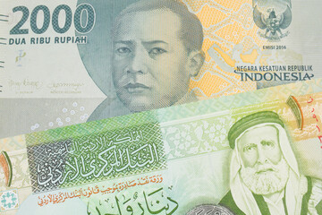 A macro image of a grey two thousand Indonesian rupiah bank note paired up with a green and yellow one dinar note from Jordan.  Shot close up in macro.