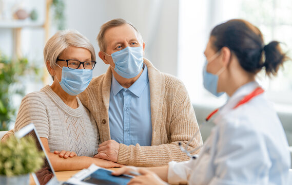 Doctor and senior couple wearing facemasks