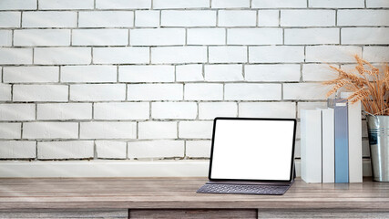 Mockup blank screen tablet on wooden table with white brick wall, copy space.