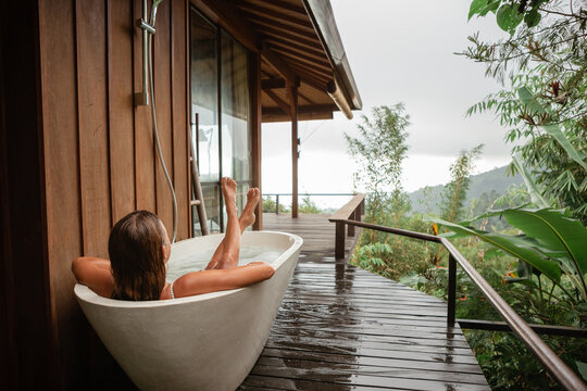 Back view woman pampering her body in water while lie in bath tube outdoor with jungle and mountains view