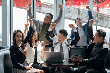 Selective focus of a Businessman raising arms to celebrate business success with his colleague in...