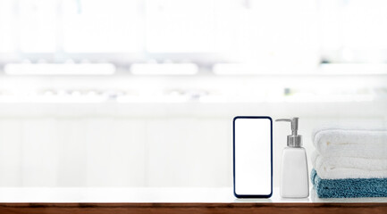 Mockup blank screen smartphone with soap bottle and clean towels on white top table in bath room, copy space.