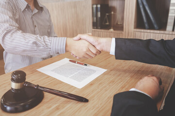 Lawyer consultant shaking hand with client in law firm.
