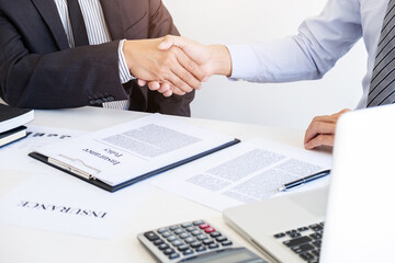 Insurance agent handshake with customer successful contract agreement.