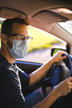 portrait of attractive nerd in long sleeve glasses and protective face mask in electric car at sunset