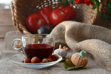 red flower tea in glass cup on burlap with knitted pumpkins on background of red vegetables