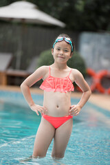 smiling child wearing swimming glasses in swimming pool. little girl playing in outdoor swimming...