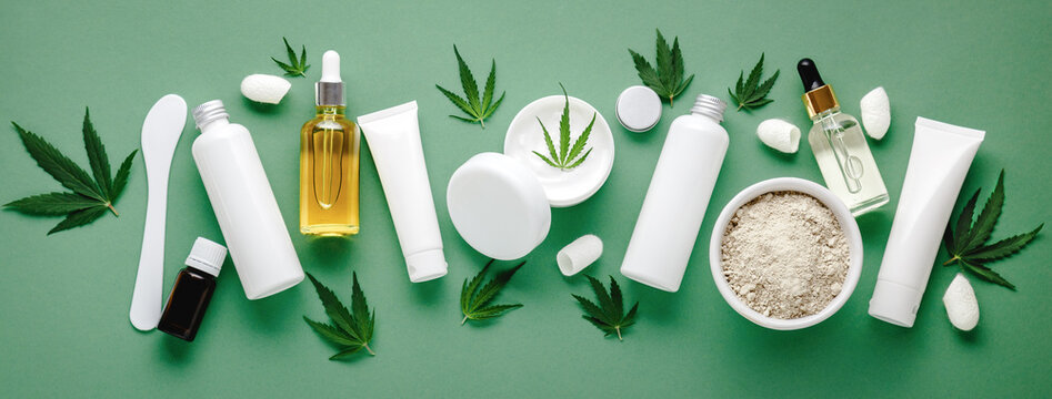 Set of hemp skin care cosmetics in white mockup packaging. Moisturizing cream, Serum, lotion, CBD oil, essential oil cannabis leaves. Flat lay long web banner copy space. on green background.