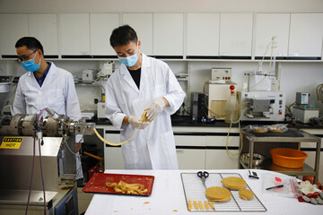 A food scientist rolls texturized vegetable protein, which is the base of the plant-based meat products offered by Zhenmeat, during a demonstration for the media of the production process in a lab at the Chinese Academy of Agricultural Sciences in Beijing