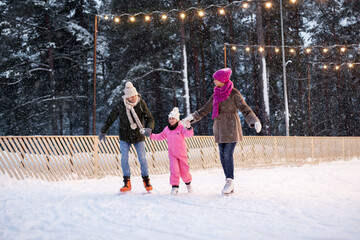 christmas, family and leisure concept - happy mother, father and daughter at outdoor skating rink in winter