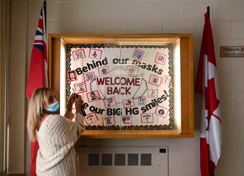 A teacher places the finishing touches on the welcome sign at Hunter's Glen Junior Public School in Scarborough