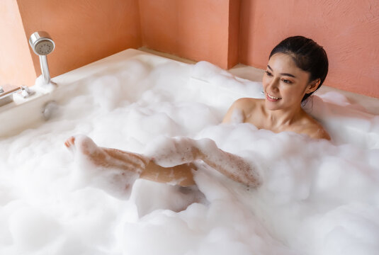 woman relaxing and takes bubble bath in bathtub with foam