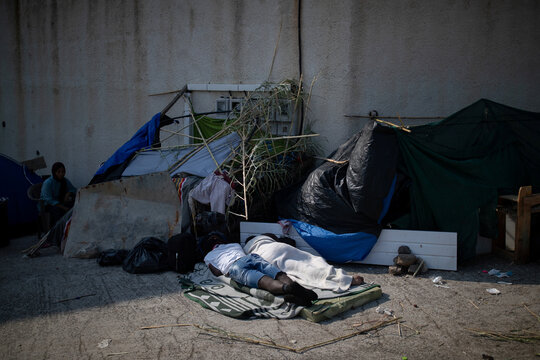 Two men sleep as refugees and migrants from the destroyed Moria camp are sheltered near a new temporary camp, on the island of Lesbos