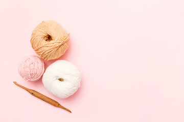 White and brown knitting wool and crochet hook on pink pastel background. Top view, flat lay, copy space