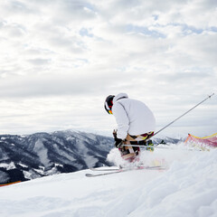 Male skier in winter jacket sliding down snow-covered slopes on skis. Man freerider in helmet skiing on fresh powder snow in winter high mountains.