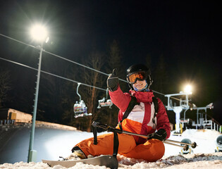 Girl skier wearing vivid suit sitting on snow-covered ski slope under illuminated chairlift at night, showing thumb up happy and satisfied after freeride at ski resort. Concept of extreme sport