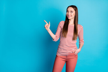Photo of positive girl promoter point index finger copyspace indicate advert promo recommend suggest select wear casual style outfit isolated over blue color background