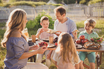 Positive family people mom dad little kids children sit table enjoy summer outside countryside meal daddy share plate sandwiches son mom hold bold strawberries rest relax concept