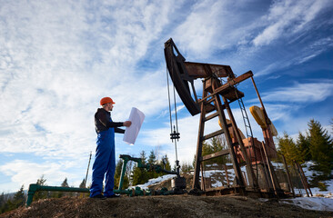Oil engineer in a blue uniform and orange helmet standing in an oilfield with a printed plan next to the oil pump jack looking at the rig, on a beautiful sunny day. Concept of oil and gas industry