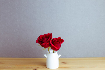 Red rose flowers in vase on wooden table with gray background. floral arrangement, copy space