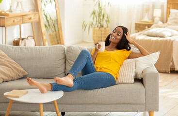 Beautiful young black woman relaxing on sofa with cup of coffee at home
