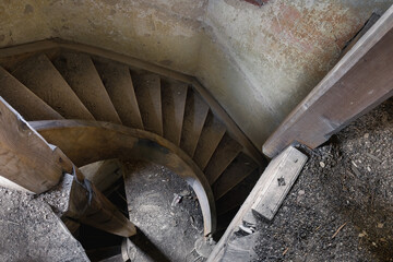 Interior with a spiral staircase in an old abandoned house