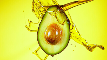 Fresh cut avocado with oil stream. Concept of healthy fruit also useful in cosmetics.