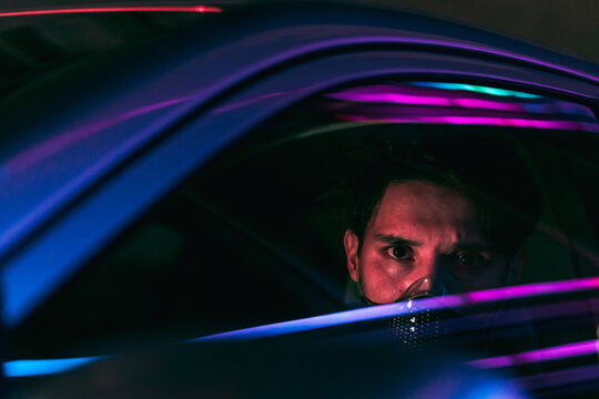 a young man in a face mask driving a car in the night city with neon lights reflecting from the glass of his car