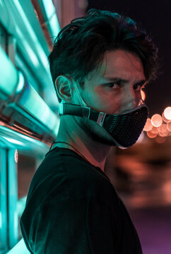 a young man in a face mask leaning on the neon display at night in a city