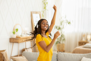 Happy young black woman with headphones and mobile device dancing to her favorite music at home