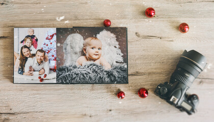 cute baby christmas angel and young family in retro photo book