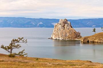 Siberian Baikal Lake. Olkhon Island in September. View of the natural landmark Shamanka Rock or Cape Burhan in the sunset light. Beautiful natural background