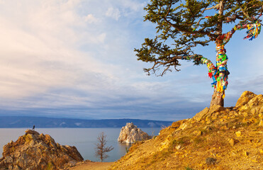 Baikal  Lake in September. Olkhon Island. The famous Wish Tree with colorful tourist ribbons in the sunset light. Tourist photographer (out of focus) climbed a cliff to shoot a beautiful landscape