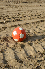 Soccer ball on dirty earth outdoor