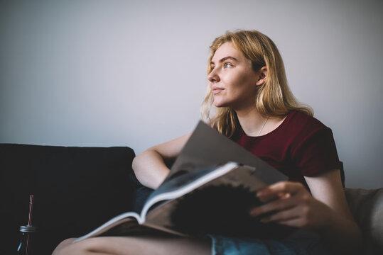 Thoughtful female reading magazine on sofa at home