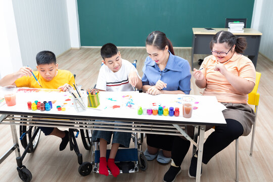 asian group of disabled kids or autism child learning and painting at paper with teacher helping in classroom