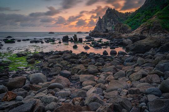 Volcanic rock boulders sitting on Watulumbung beach in Gunung Kidul, Yogyakarta, Indonesia with golden sunset sky