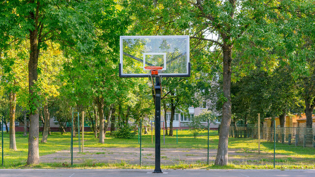 backboard on metal pole on basketball playground in city park with greenery