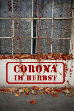 Roter Stempel, Graffiti mit Schriftzug: Corona im Herbst, ist im Herbst, als Warnung, auf eine Mauer von einem alten Haus, gestempelt.