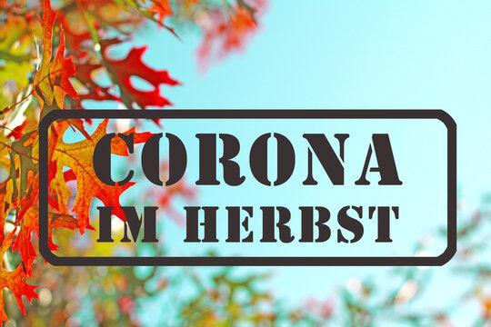 Stempel in Anthrazit, mit Schriftzug: Corona im Herbst, ist im Herbst, als Warnung, auf blauem Himmel, vor Ast mit schönem gelben und orangen Herbslaub, gestempelt.