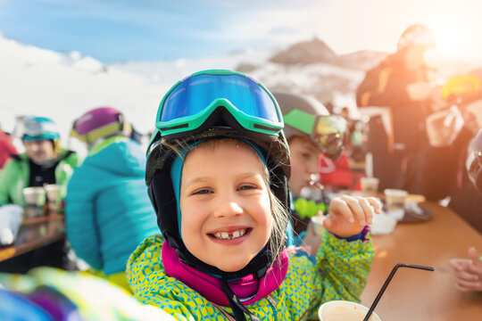 Cute adorable happy funny caucasian little toddler boy enjoy having family fun and making selfie with phone at alpine mountain european ski resort on sunny winter day. Playful smiling child portrait