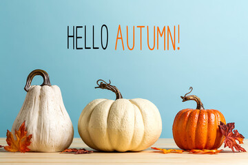 Hello autumn message with pumpkins on a blue background