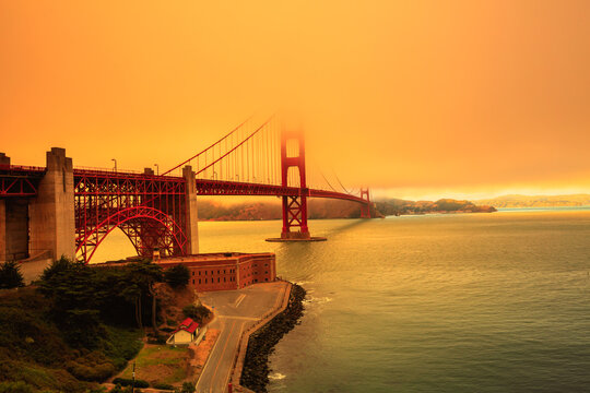 Smoky orange sky on Golden Gate Bridge of San Francisco skyline from Fort point. Californian fires in September 2020 in United States. Wildfires composition.