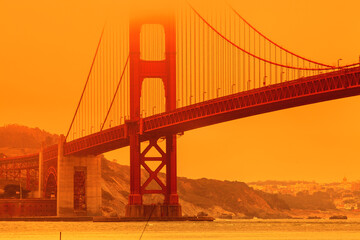 Bottom view of smoky orange sky on Golden Gate Bridge of San Francisco city from Lime point. California fires in September 2020 in United States. Wildfires composition.