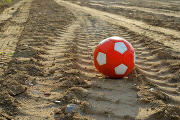 Used red and white soccer ball on dirty earth
