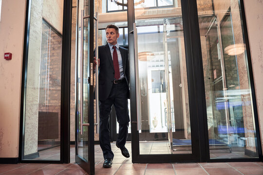 Businessman in suit opening office door
