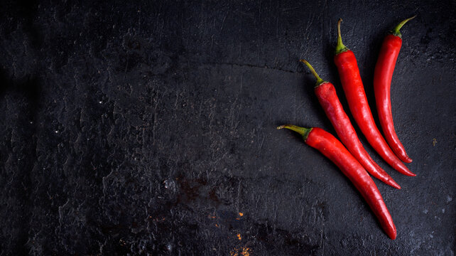 Red hot chili peppers on black rustic textured slate from above. Food background with spicy chilli paprika.